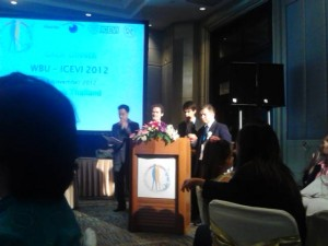 "Michael and James on stage with projecter screen showing ""Gala dinner WBU-ICEB 2012"""