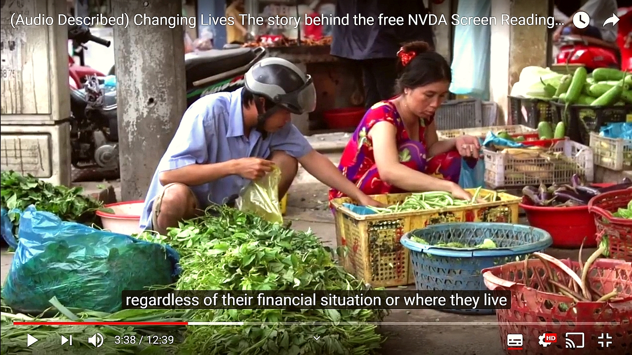 "Screenshot from ""Changing Lives: The story behind the free NVDA screen reader"".  People in a market in Vietnam, subtitle text ""regardless of their financial situation or where they live""."