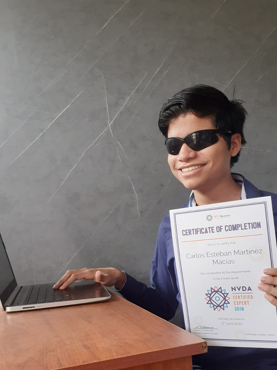 Carlos Esteban Martínez Macías holding his NVDA Certified Expert Certificate and with his hand on PC keyboard